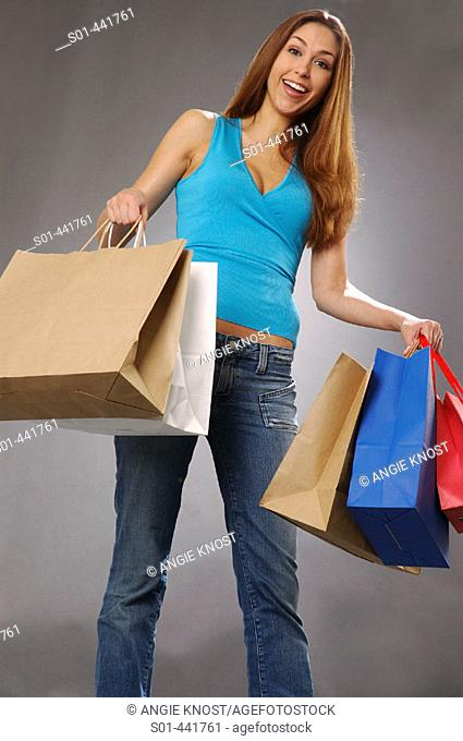 Happy young woman with many shopping bags