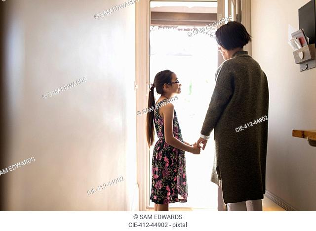 Affectionate mother and daughter holding hands in doorway