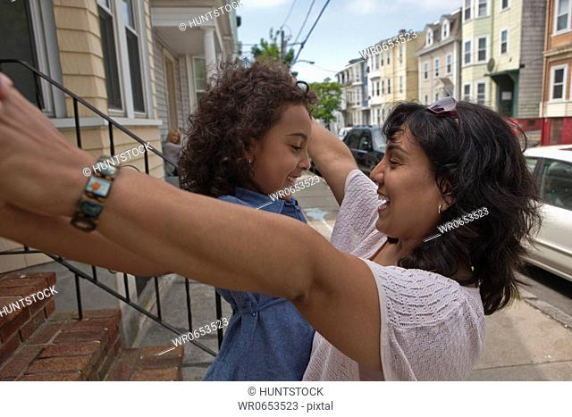 Hispanic woman playing with her daughter in front of her house