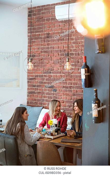 Three female friends, sitting together in cafe