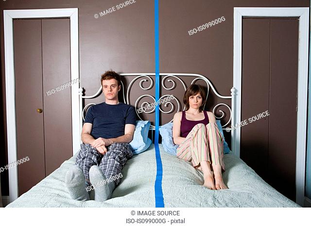 Young couple sitting on bed separated by blue line
