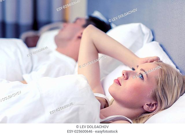 hotel, travel, relationships, and problems with sleep concept - family couple in bed, woman with insomnia