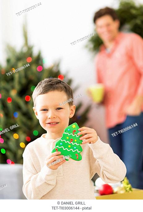 Boy (6-7) holding gingerbread