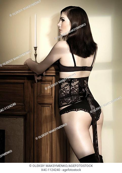 Beautiful woman in black lingerie standing at a fireplace