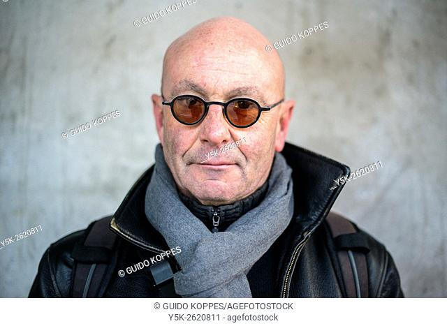 Rotterdam, Netherlands. Portrait of a balding, middle aged man wearig glasses in front of a concrete pillar