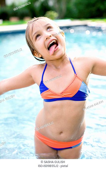 Girl standing in outdoor swimming pool sticking out tongue