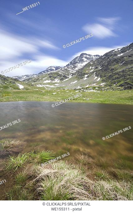 Lake Emet surrounded by green meadows and peaks Montespluga Chiavenna Valley Sondrio province Valtellina Lombardy Italy Europe