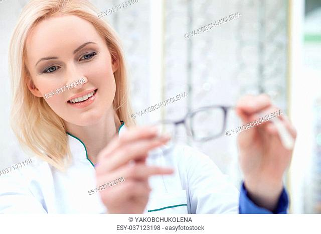 Waist up portrait of professional young optician serving the customer in shop. The woman is standing and holding eyeglasses. She is smiling
