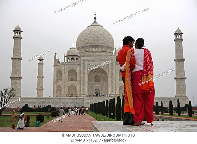 Young couple at Taj Mahal Seventh Wonders of World on the south bank of Yamuna river , Agra , Uttar Pradesh , India UNESCO World Heritage Site