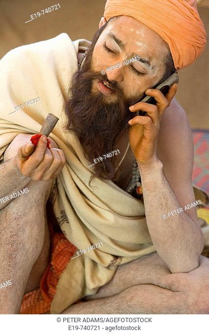 Sadhu with chillum pipe & mobile phone, Allahabad, Uttar Pradesh, India
