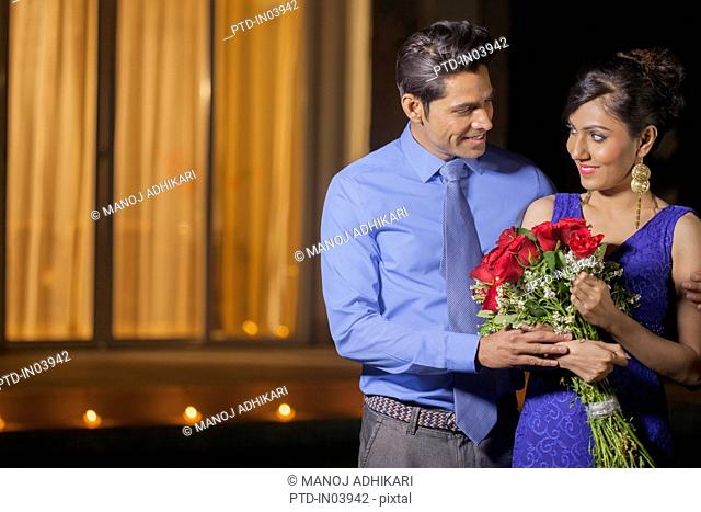 India, Man wearing shirt and tie with woman in blue evening dress holding red roses