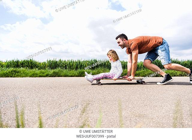 Father pushing daughter on skateboard