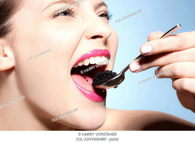 Smiling woman eating caviar