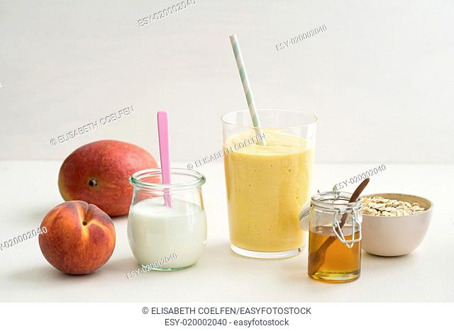 Healthy orange breakfast smoothie with yogurt, peach, mango, honey and oats in a glass