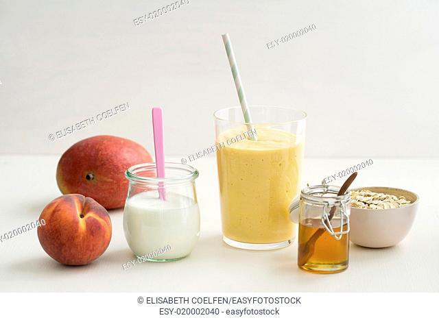 Healthy orange breakfast smoothie with yogurt, peach, mango, honey and oats in a glass