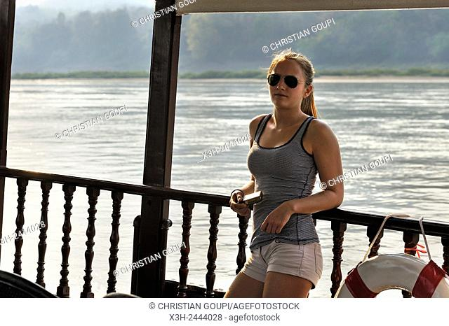 young woman standing at the railing of a cruise boat, owned by '' The Luang Say Lodge & Cruises'', on Mekong River, between Pakbeng and Luang Prabang