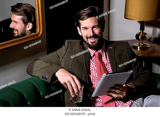 Portrait of man holding digital tablet and drinking glass