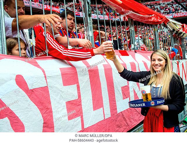 A young woman hands mugs of free beer to fans prior to the German Bundesliga soccer match between FC Bayern Munich and FSVMainz 05 at the Allianz-Arena in...
