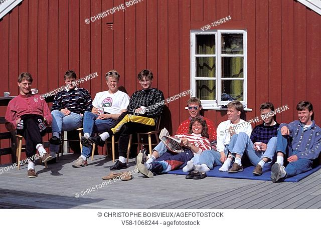 Norway, Nordland, Lofoten Islands, Stamsund, Students sunbathing before a Rorbu or fishing cabin