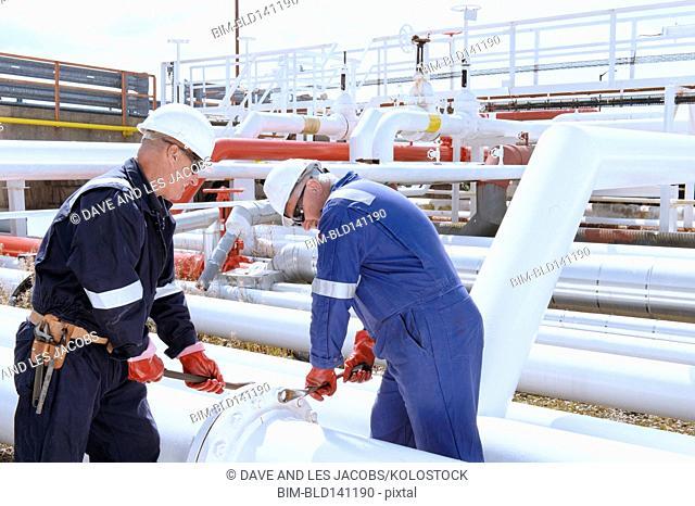 Caucasian technicians tightening bolts on pipe