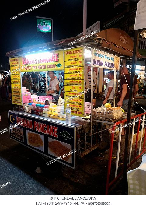 """05 March 2019, Thailand, Karon Beach: A booth offering the traditional Thai dessert """"""""Roti"""""""" at temple market in Karon Beach"""