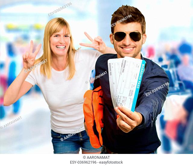 Man Holding Boarding Pass In Front Of Happy Woman Gesturing, Indoor