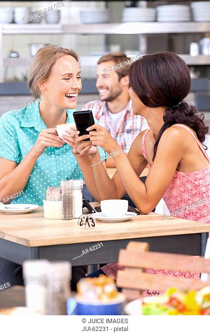 Laughing friends texting with cell phone in coffee shop