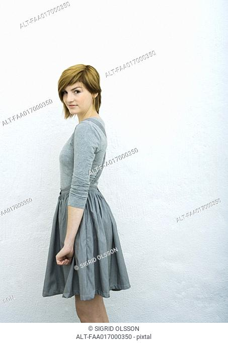Young woman standing, looking at camera, side view, portrait