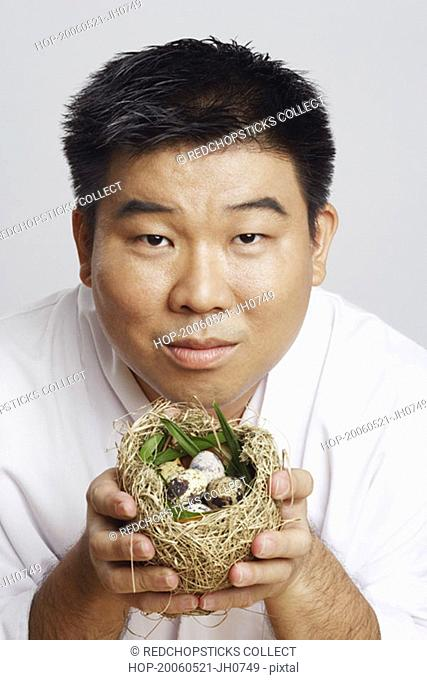 Portrait of a mid adult man holding a bird's nest