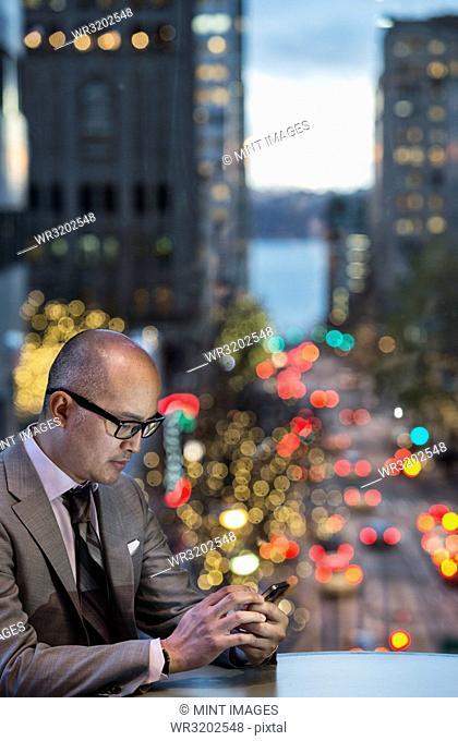 A side view of an Asian businessman sitting at a table working on his phone in front of a window with a view to a city street at dusk