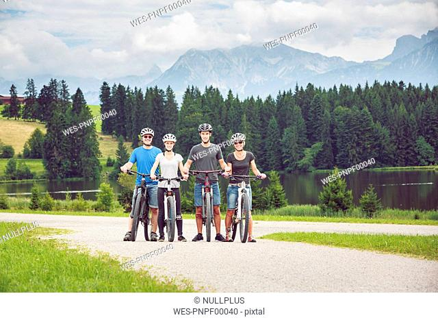 Germany, Bavaria, Pfronten, portrait of happy family with mountain bikes at ladeside
