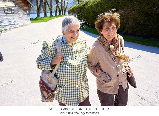 light-hearted old senior woman walking together arm in arm