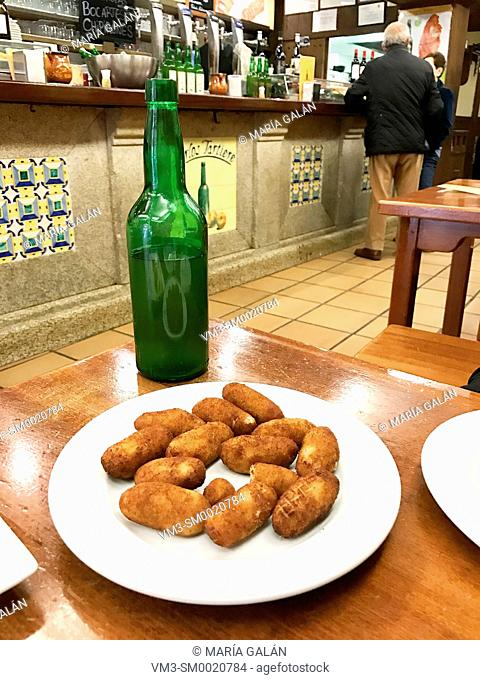 Croquettes serving with bottle of cider in a restaurant. Madrid, Spain