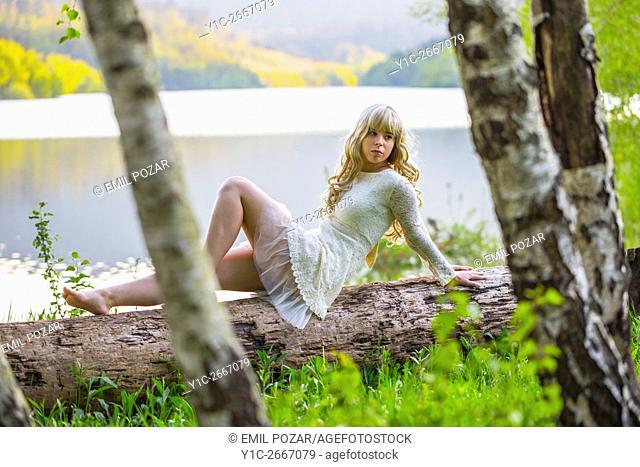 Evening chill on lake teen girl in fancy dress