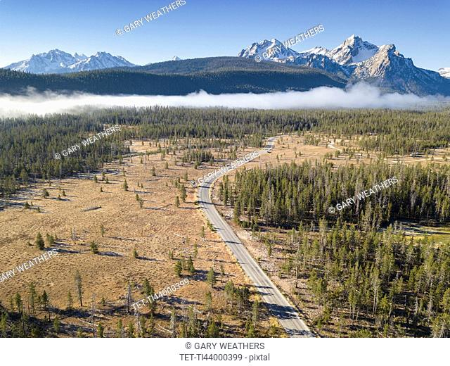 USA, Idaho, Sawtooth Range, Road in forest with snowcapped mountains in background
