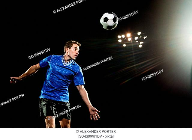 Young man leaping to head soccer ball