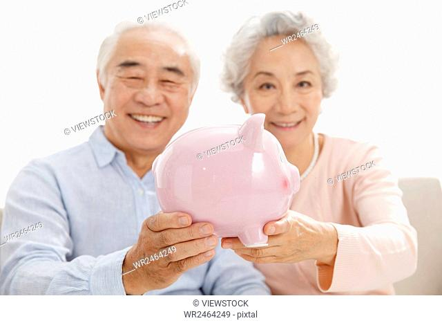 Portrait of senior couple with piggy bank