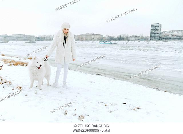 Serbia, Petrovaradin, white dressed young woman with white dog at riverside