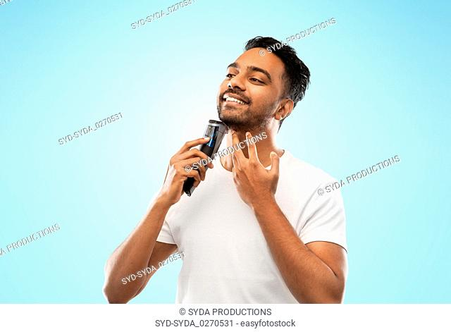 smiling indian man shaving beard with trimmer