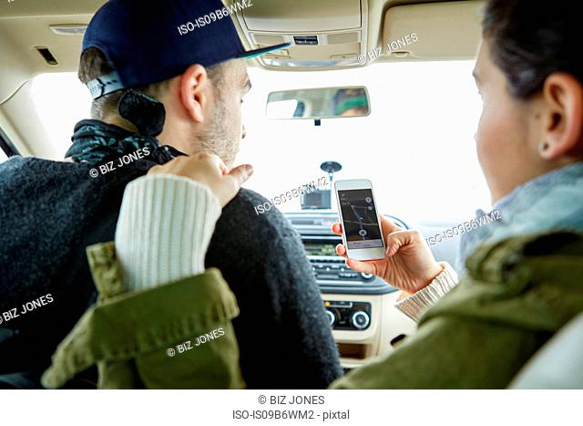 Young couple sitting in car, woman holding smartphone with map on screen, rear view