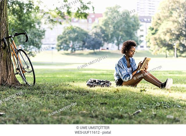 Young woman resting in park using tablet