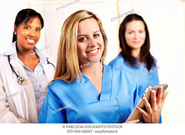 Portrait of a smart young female nurse standing in front of his team and smiling