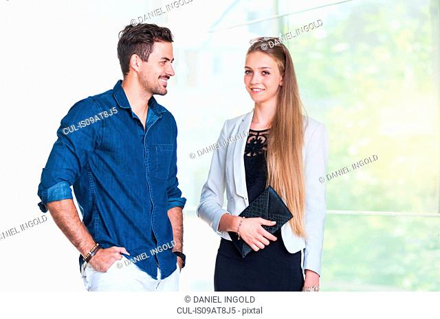 Young couple talking in front of window in city