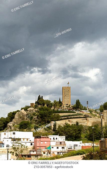 Dark rain clouds over the Arabic castle tower (Torre del Homenaje), Velez Malaga,
