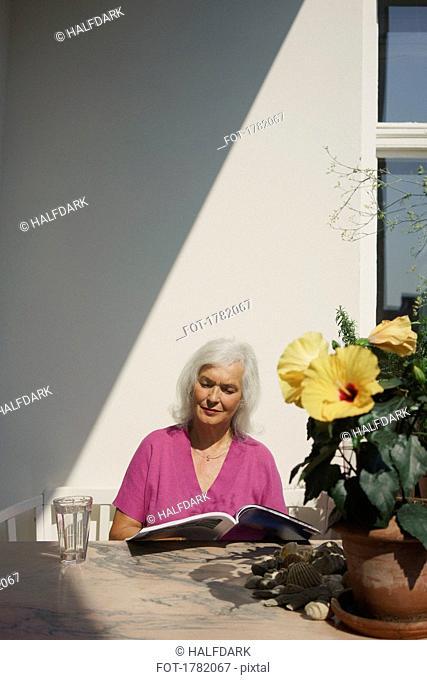 Senior woman reading magazine on sunny patio