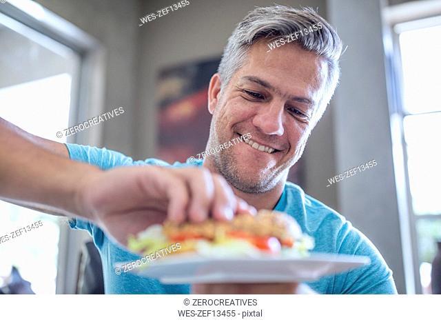 Man having a sandwich from plate