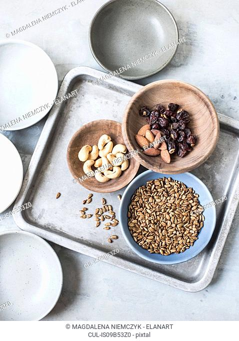 Studio shot, overhead view of cashew nuts, almonds, seeds and dried fruit in bowls