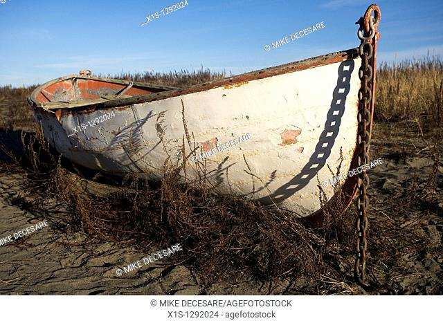 Old wooden lifeboat beached in the sand with its anchor chain seeming to hold it on the beach