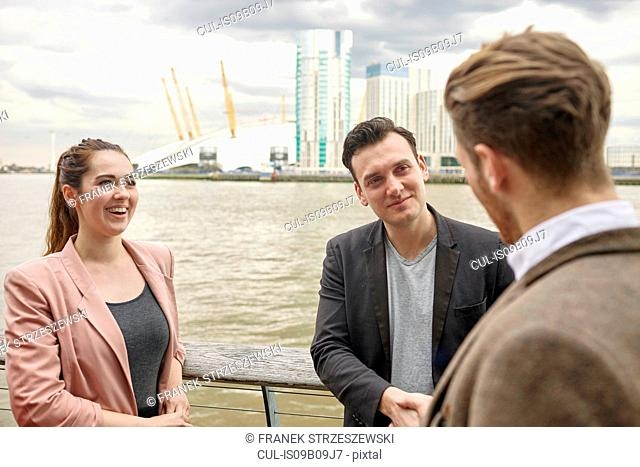 Young businesswoman and businessmen having discussion on waterfront, London, UK