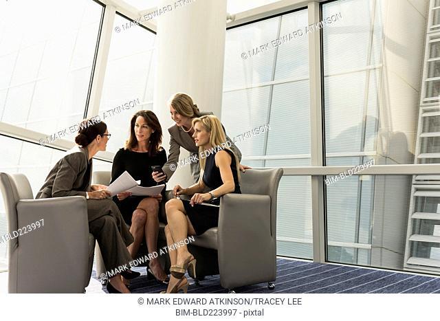 Caucasian businesswomen sitting in armchairs talking